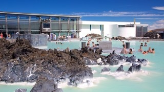 Blue Lagoon which includes a hot spring and a luxury hotel or resort as well as a large group of people