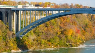 Rainbow Bridge showing a river or creek, a bridge and autumn leaves