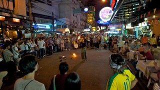 Khao San Road which includes signage, nightlife and street scenes
