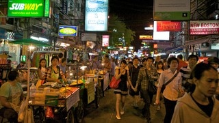 Khao San Road which includes signage, night scenes and street scenes