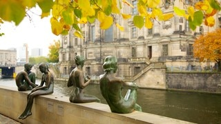 Berlin Cathedral which includes religious elements, fall colors and a statue or sculpture