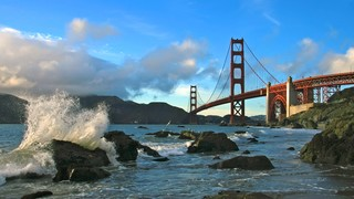Baker Beach which includes a bridge, rugged coastline and landscape views