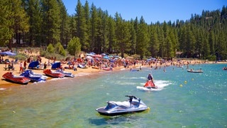 Zephyr Cove Beach showing jet skiing, a sandy beach and forest scenes