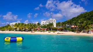 Doctor's Cave Beach featuring tropical scenes, a sandy beach and a coastal town