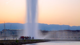 Jet d'Eau Fountain showing a sunset and a fountain as well as a large group of people