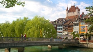 Thun Castle showing a bridge, a river or creek and a castle