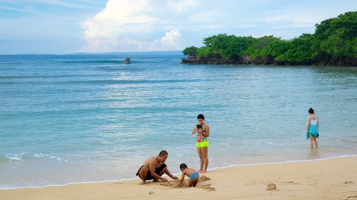 Nusa Dua Beach featuring tropical scenes and a beach as well as a small group of people