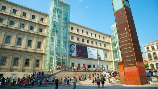Reina Sofia Museum which includes a square or plaza and modern architecture as well as a large group of people