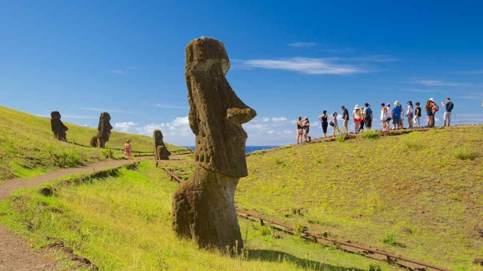 Rano Raraku featuring a statue or sculpture and heritage elements as well as a small group of people