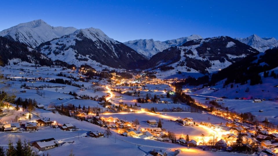 Gstaad showing night scenes, snow and a small town or village