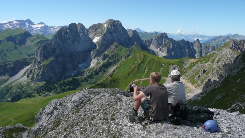 Gstaad which includes a gorge or canyon and mountains as well as a small group of people