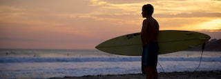 Zicatela Beach which includes a sunset, a beach and surfing