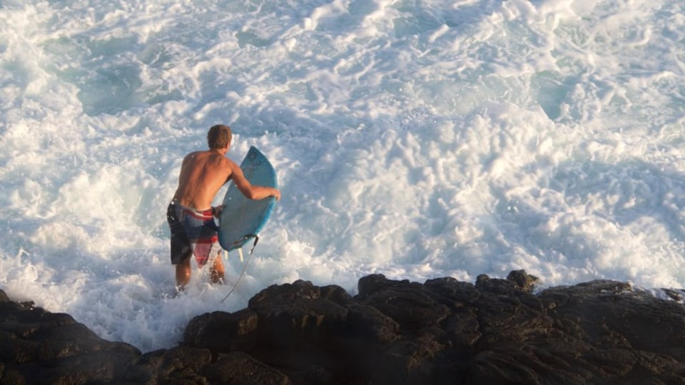 Kailua-Kona featuring surfing and rugged coastline as well as an individual male