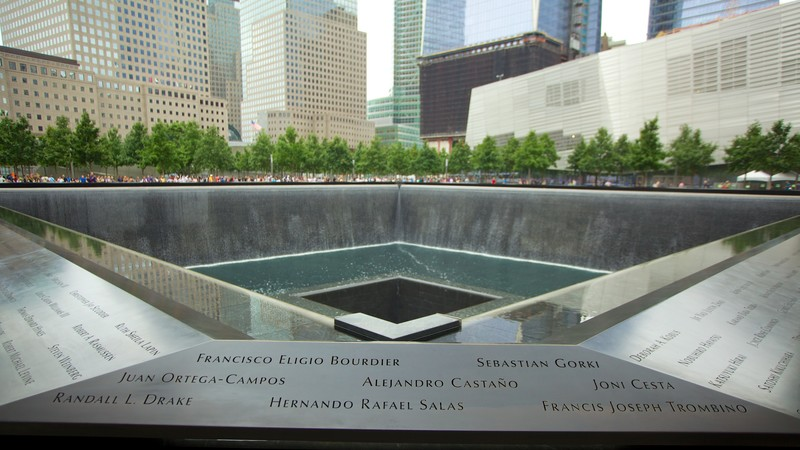 The National September 11 Memorial featuring a memorial and a city
