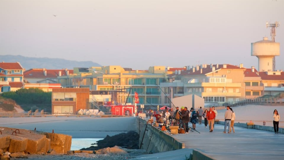 Barra Beach featuring a sunset and a coastal town as well as a small group of people