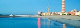 Barra Beach featuring a coastal town, a lighthouse and general coastal views