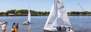Bay City showing sailing and a lake or waterhole as well as a small group of people