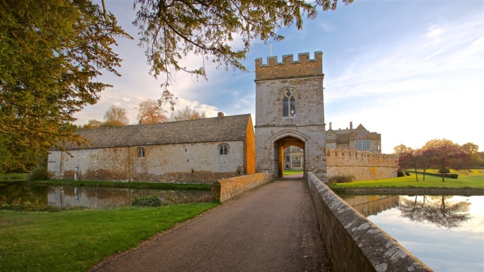 Broughton Castle which includes a lake or waterhole, a sunset and chateau or palace