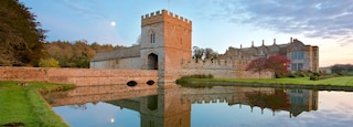 Broughton Castle featuring a sunset, a lake or waterhole and heritage architecture