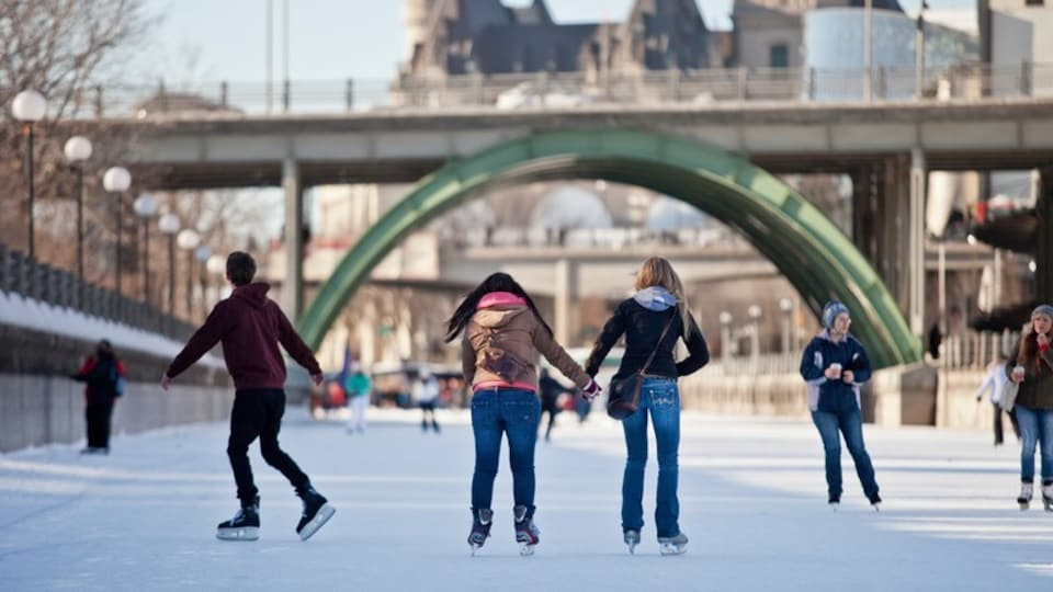 Rideau Canal which includes a bridge and ice skating as well as a small group of people