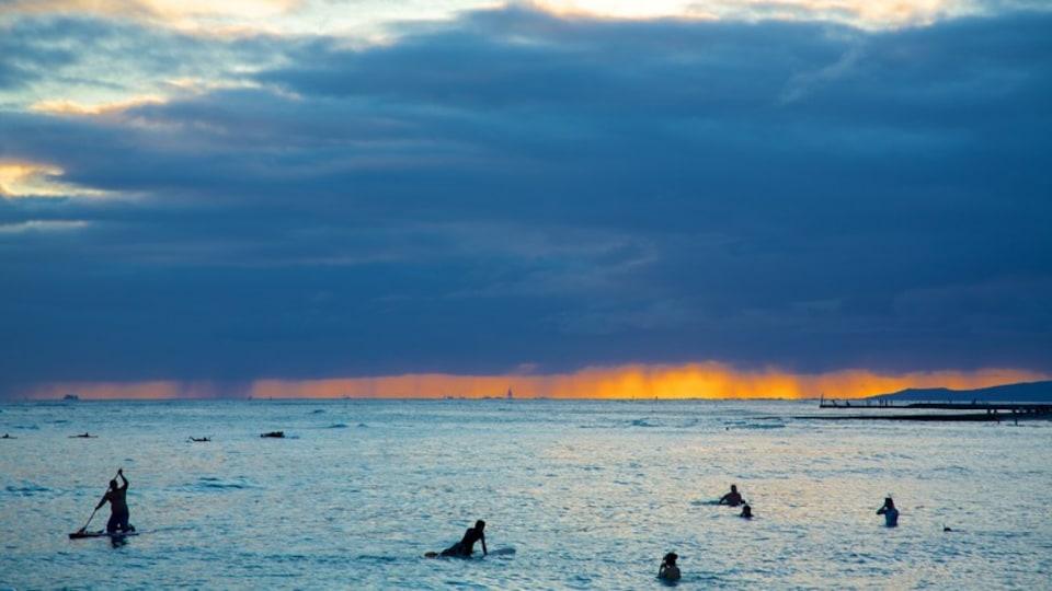 Waikiki Beach showing surfing, a sunset and general coastal views