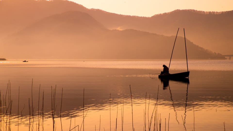 Lake Kawaguchi which includes a sunset, a lake or waterhole and fishing