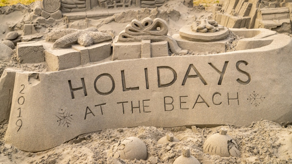 Long Beach showing outdoor art, a sandy beach and signage