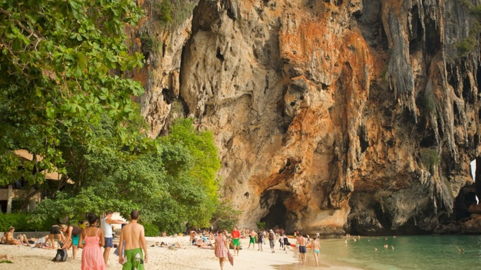 West Railay Beach featuring a sandy beach and a gorge or canyon as well as a large group of people