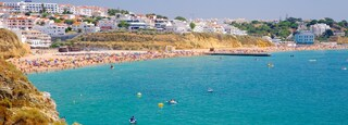 Albufeira showing a sandy beach, swimming and a coastal town