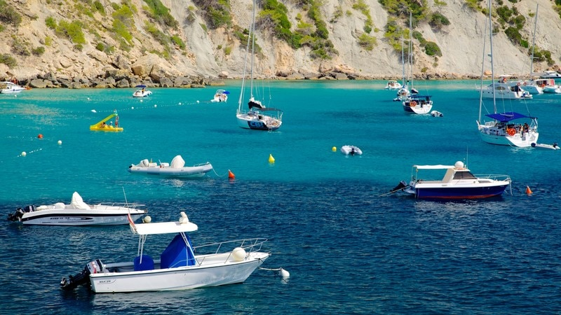 Cala d\'Hort Beach featuring rocky coastline, boating and a marina