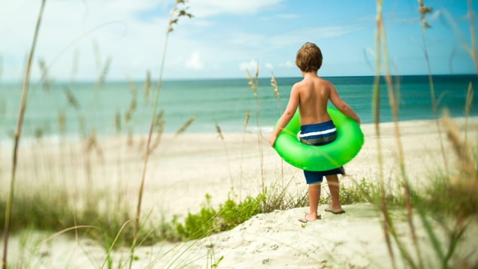 Morehead City featuring a sandy beach as well as an individual child