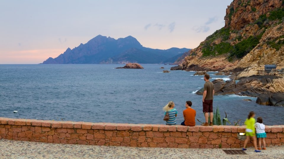 Porto Beach which includes rugged coastline and a sunset as well as a small group of people