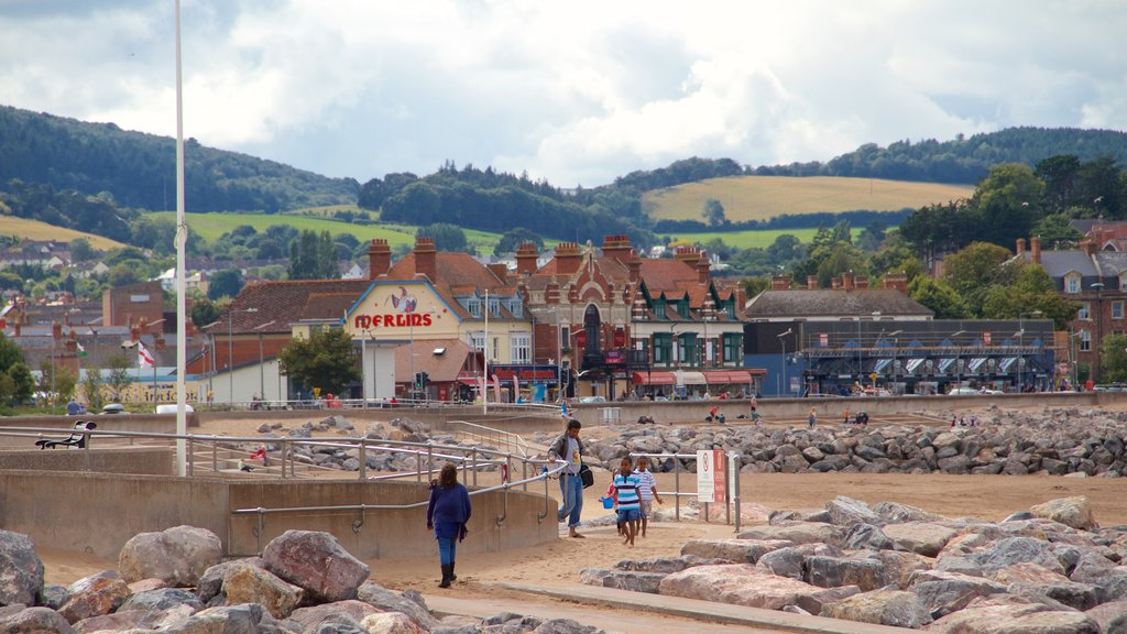 Minehead showing a sandy beach and a coastal town as well as a small group of people