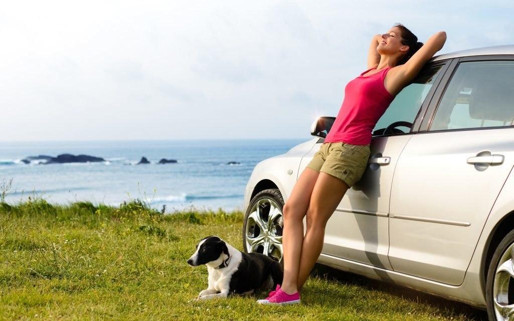 Frau entspannt mit Hund neben Auto, stressfreie Anreise mit dem Auto