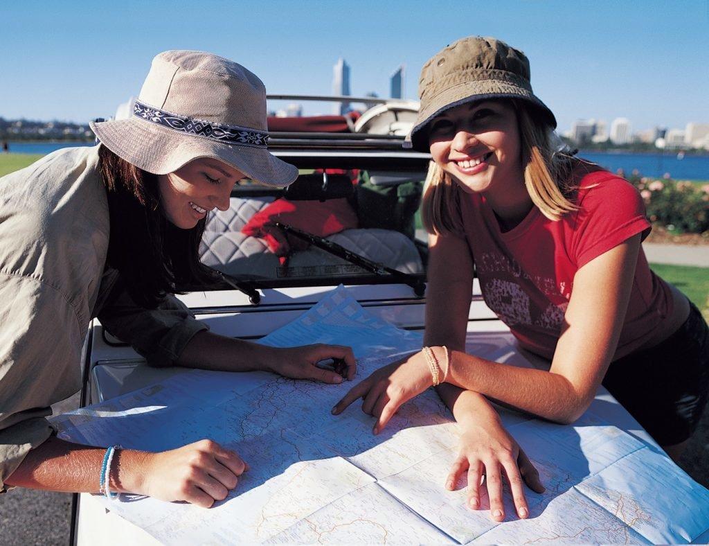 Freundinnen mit Landkarte auf Motorhaube