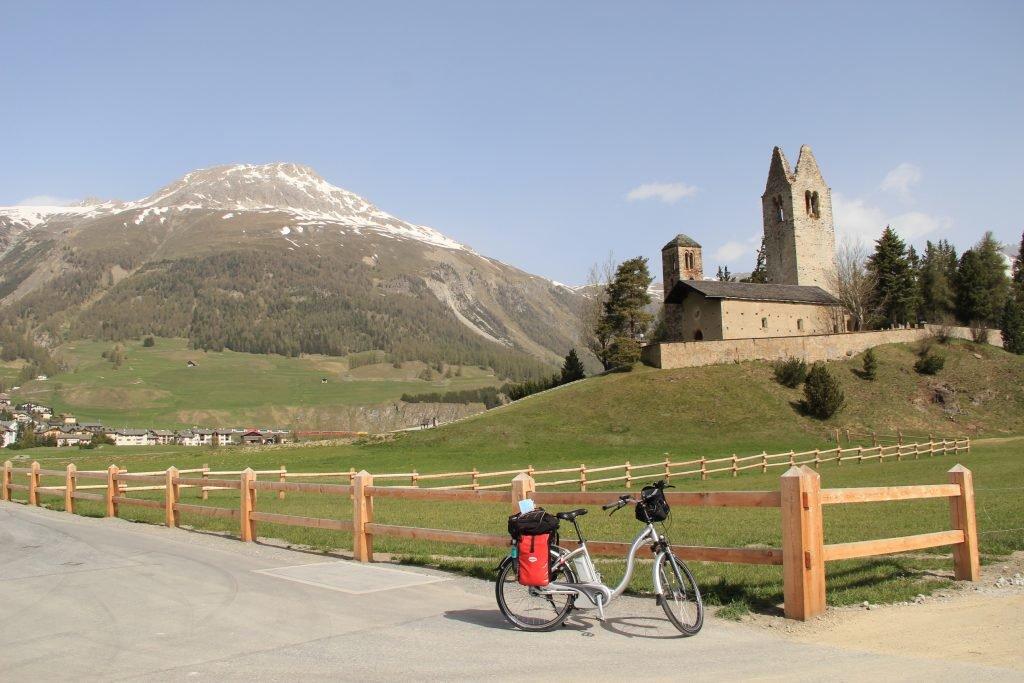 Schweizer Landschaft mit Kirche, Alpen und Fahrrad