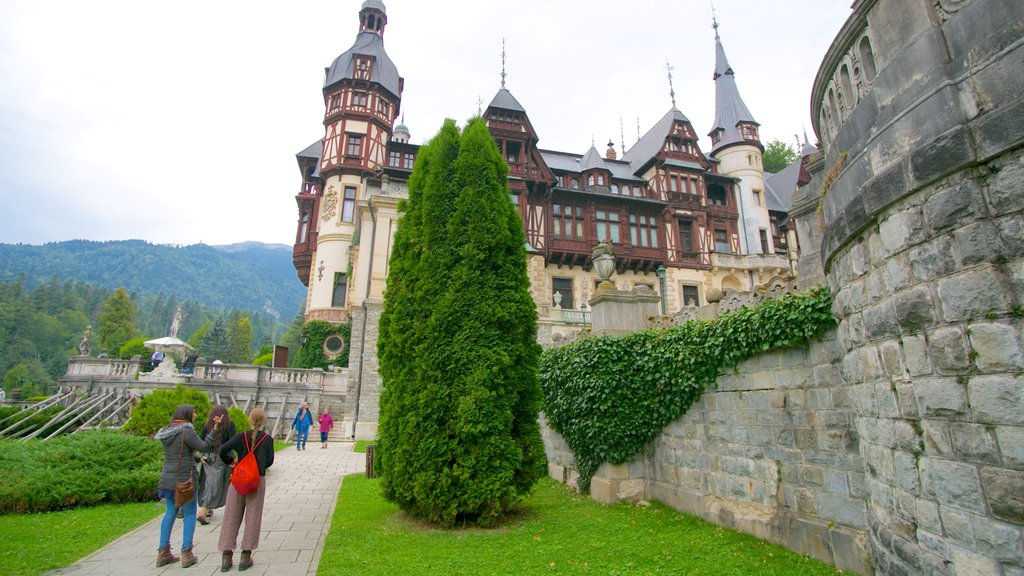 Peles Castle featuring a castle and heritage architecture as well as a small group of people