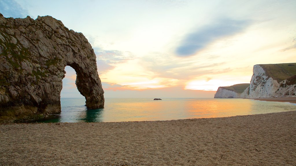 Durdle Door featuring a sunset and a pebble beach