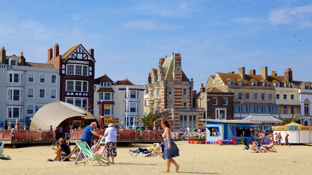 Weymouth Beach showing a house and a sandy beach as well as an individual femail