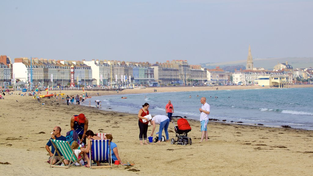 Weymouth Beach featuring a beach as well as a small group of people
