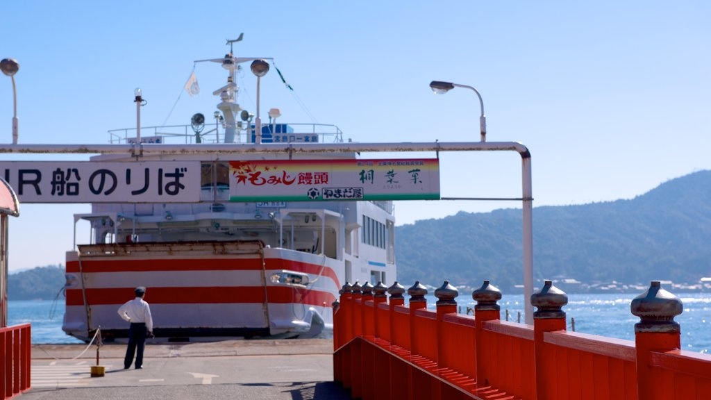Miyajima Ferry Terminal showing general coastal views and boating as well as an individual male