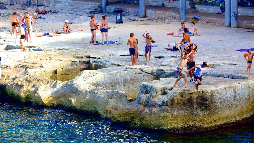Sliema featuring swimming and rocky coastline as well as a large group of people