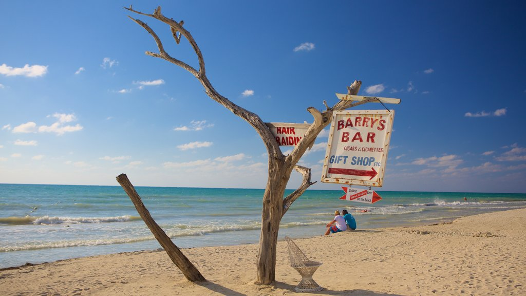 Seven Mile Beach featuring signage and a sandy beach