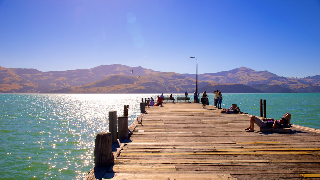 Akaroa which includes general coastal views and mountains as well as a large group of people