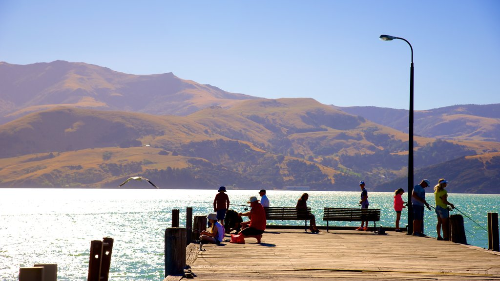 Akaroa showing mountains and general coastal views as well as a large group of people