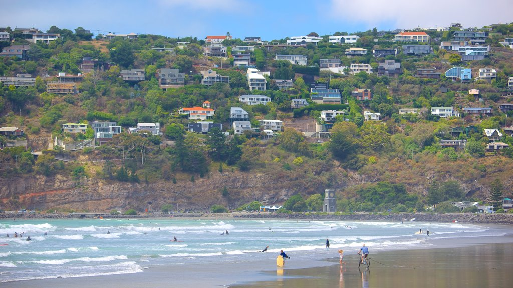 Sumner Beach showing a coastal town and a bay or harbor as well as a large group of people