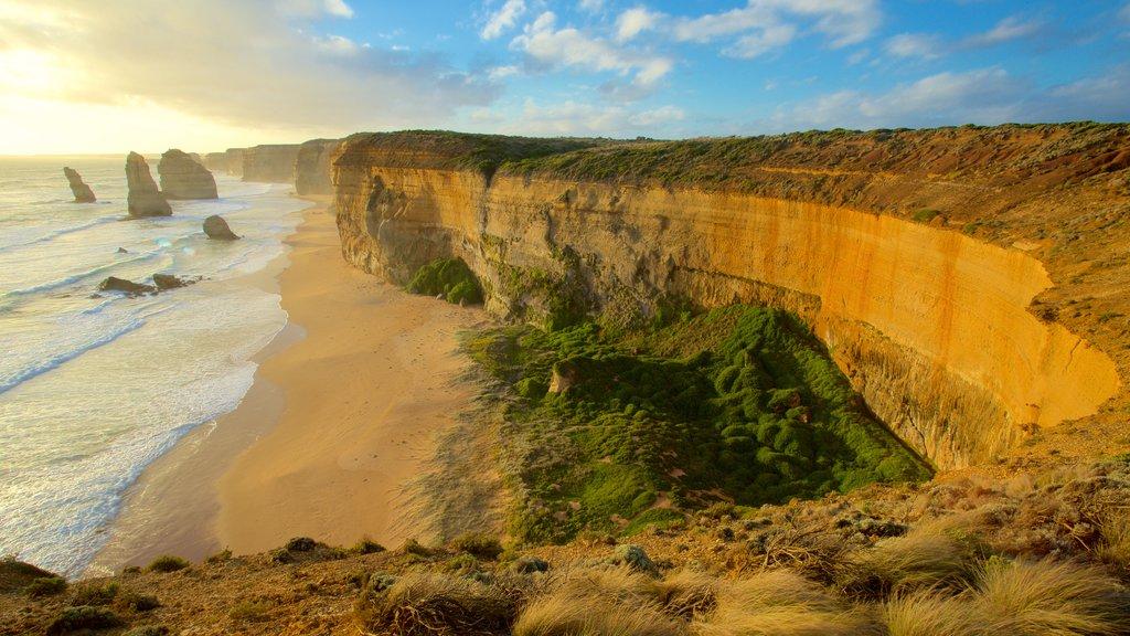 Twelve Apostles que incluye un barranco o cañón, una puesta de sol y una playa de arena