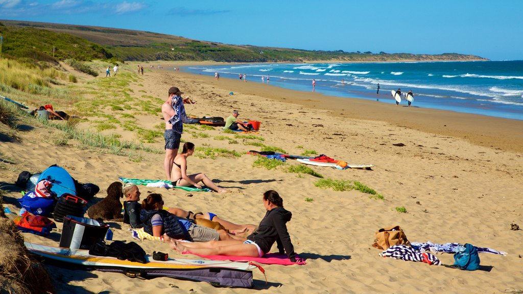 Great Ocean Road featuring a bay or harbor and a sandy beach as well as a small group of people