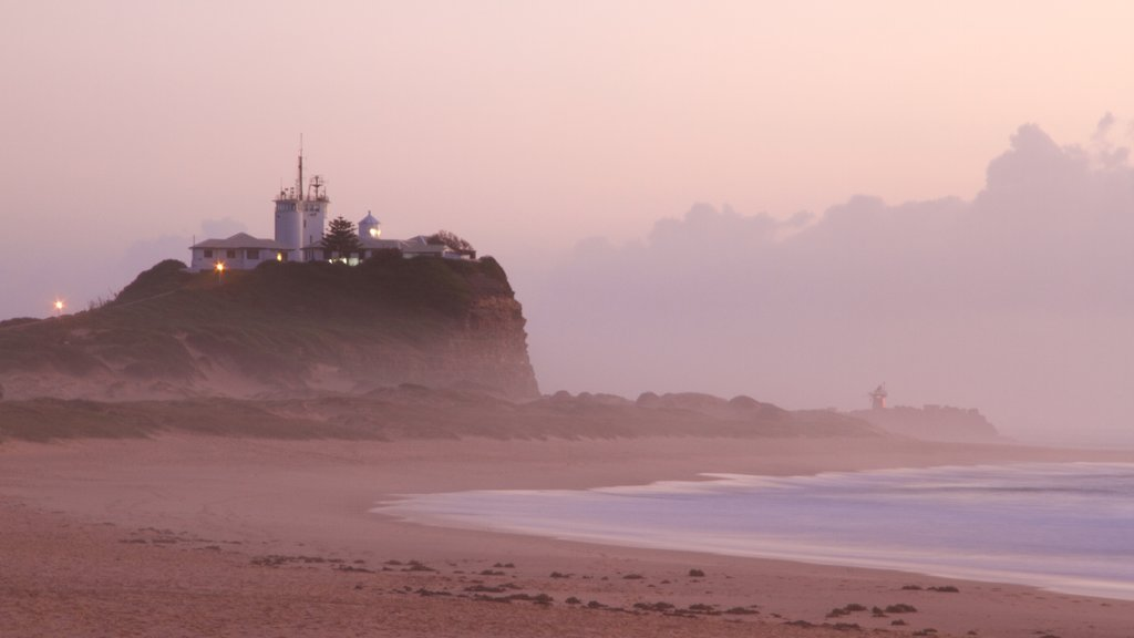 Nobbys Head Beach which includes a sandy beach, mist or fog and a lighthouse