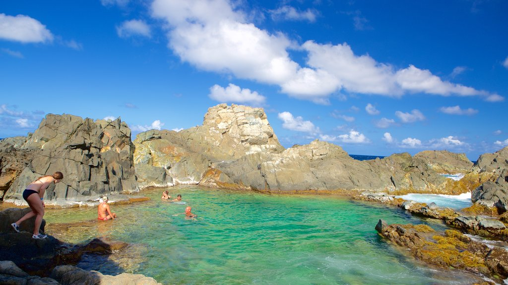Conchi Natural Pool featuring general coastal views as well as a small group of people
